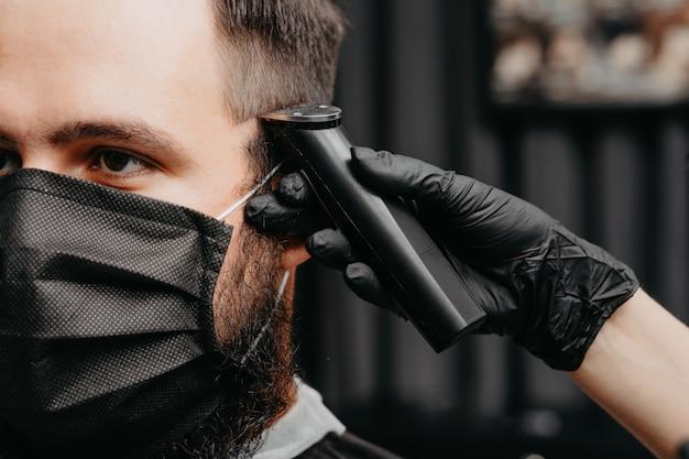Mulher barbeiro cortar cabelo para um homem barbudo em máscara facial. conceito de corte de cabelo de quarentena.
