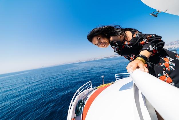 Mulher barco sorrindo feliz olhando para o mar navegando. modelo feminino caucasiano asiático.