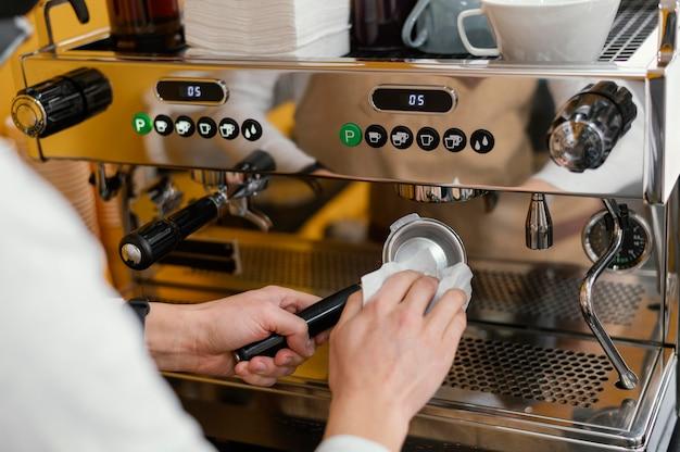 Mulher barista limpando máquina de café