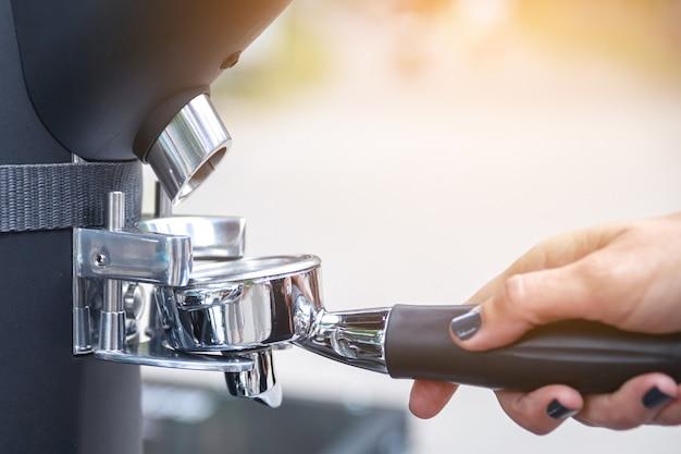Mulher barista moendo grãos de caixão preto no porta-filtro