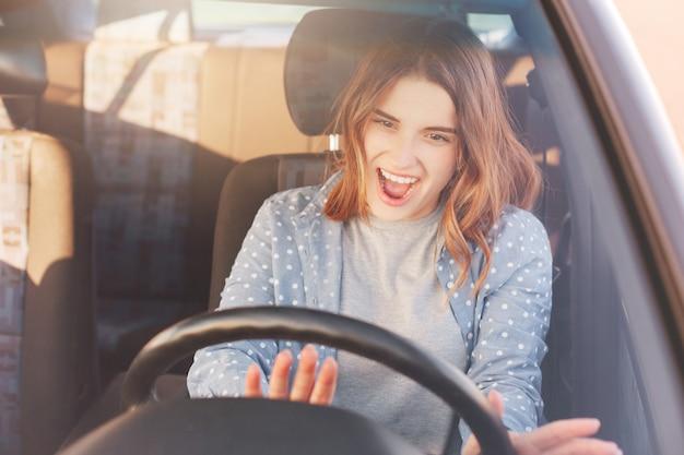 Mulher bastante atraente se diverte no carro enquanto dirige e faz viagens, ouve música favorita no rádio, gira a roda, sorri alegremente