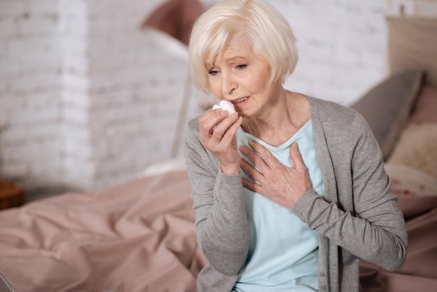 Mulher bastante idosa sentada na cama tocando seu peito enquanto tosse
