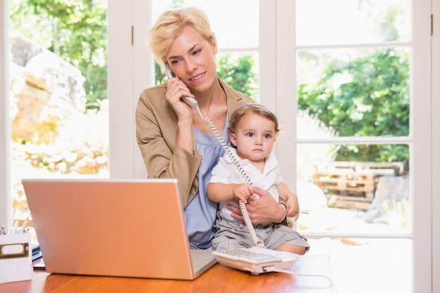 Mulher bastante loira com o filho telefonando e usando o laptop