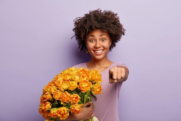 Mulher bastante otimista aponta diretamente para você com o dedo indicador, convida para vir nas férias, segura flores amarelas, veste uma camiseta casual, isolada sobre a parede roxa, tem um sorriso alegre. monocromático