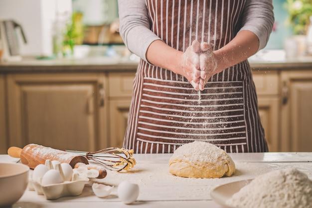 Mulher bate com as mãos acima closeup de massa. baker terminando sua padaria, sacuda a farinha de suas mãos, espaço livre para texto. padaria caseira, conceito de processo de cozimento