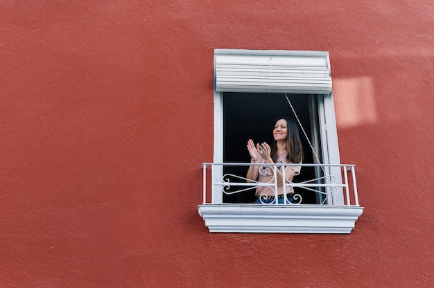 Mulher batendo palmas na janela de sua casa com a fachada vermelha