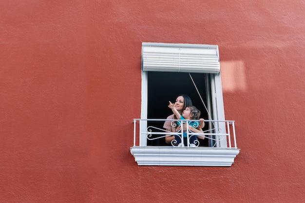 Mulher batendo palmas na janela de sua casa com a filha