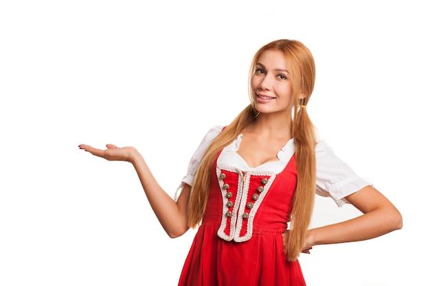 Mulher bávara de cabelos vermelha sexy linda sorrindo alegremente para a câmera segurando o espaço da cópia na mão. empregada de mesa atraente oktoberfest em vestido tradicional alemão
