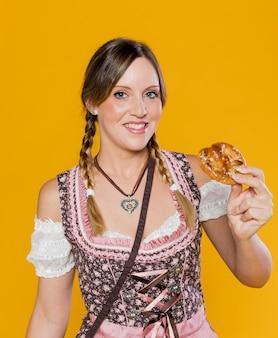 Mulher bávara do smiley com pretzel
