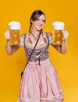 Mulher bávara feliz que guarda canecas de cerveja