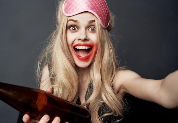 Mulher bêbada com uma garrafa de álcool deitada no sofá com os lábios manchados