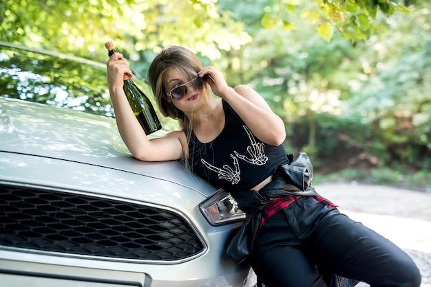 Mulher bêbada com uma garrafa parada na beira da estrada perto do carro