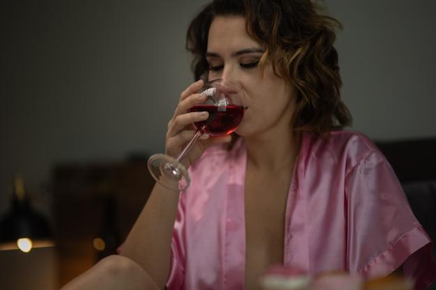 Mulher bêbada em depressão está no quarto e sofre de ansiedade bebe álcool vinho sozinha em casa