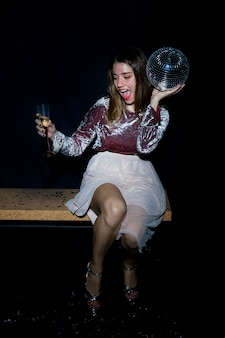 Mulher bêbada sentado no banco com bola de discoteca