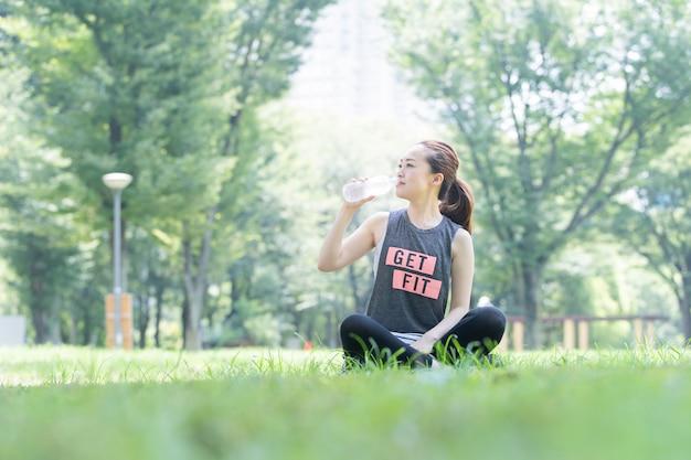 Mulher bebe água enquanto faz ioga no parque