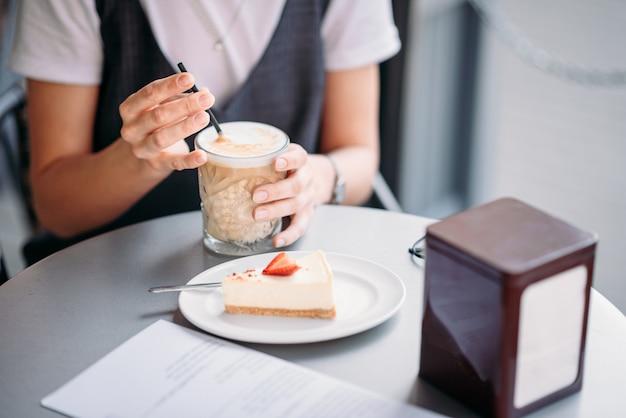 Mulher bebe café e comer bolo na mesa do café no dia de verão ao ar livre