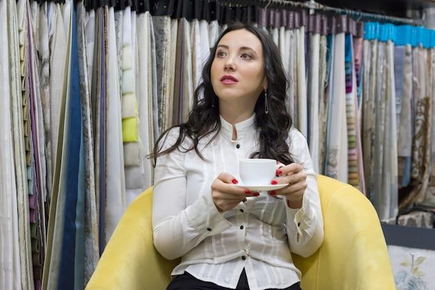 Mulher bebe café no showroom de tecidos