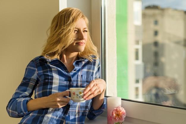 Mulher bebe café, olha pela janela em casa