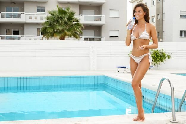 Mulher bebendo água ao lado de uma piscina