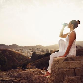 Mulher bebendo água após a ioga