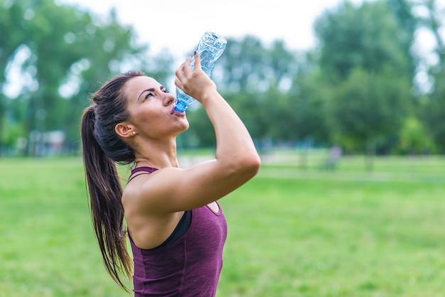 Mulher bebendo água após esporte