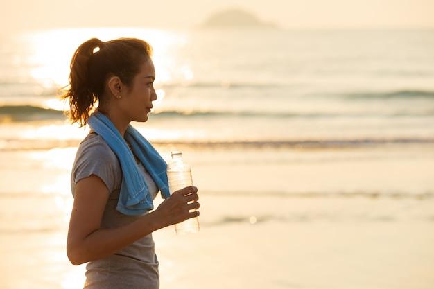 Mulher bebendo água após o exercício.