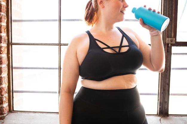 Mulher bebendo água após o treino