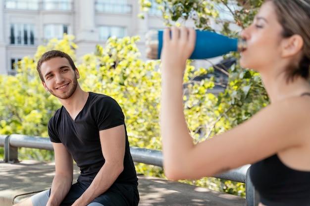 Mulher bebendo água depois de se exercitar ao ar livre com um homem