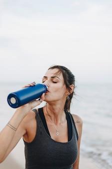 Mulher bebendo água depois de um treino