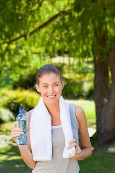 Mulher bebendo água depois do ginásio