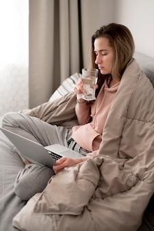 Mulher bebendo água e ficar debaixo de cobertores