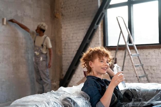 Mulher bebendo água enquanto o homem pinta a parede de sua nova casa