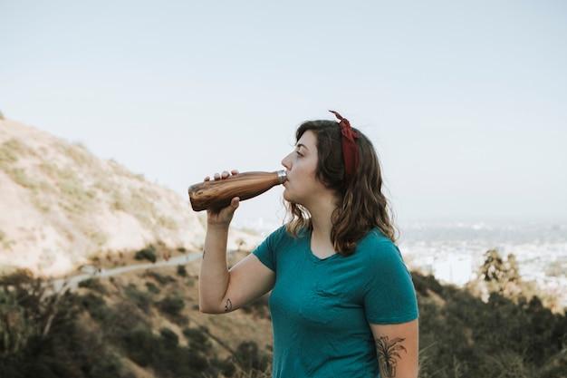 Mulher bebendo água enquanto trekking