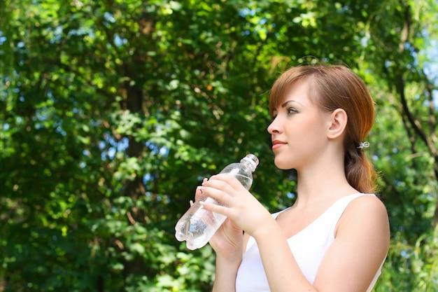 Mulher bebendo água na floresta
