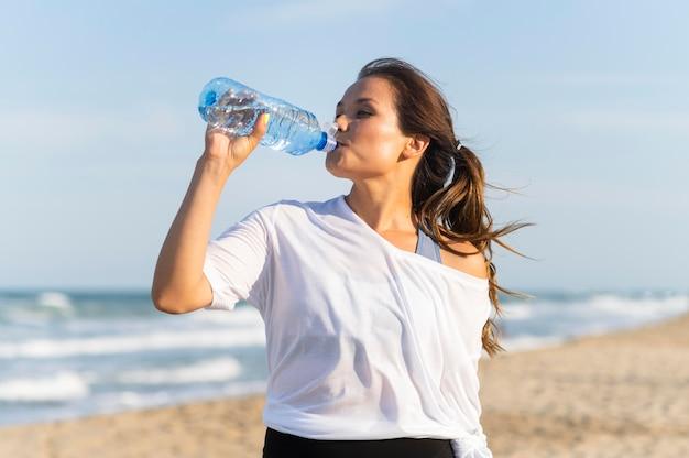 Mulher bebendo água na praia enquanto faz exercícios