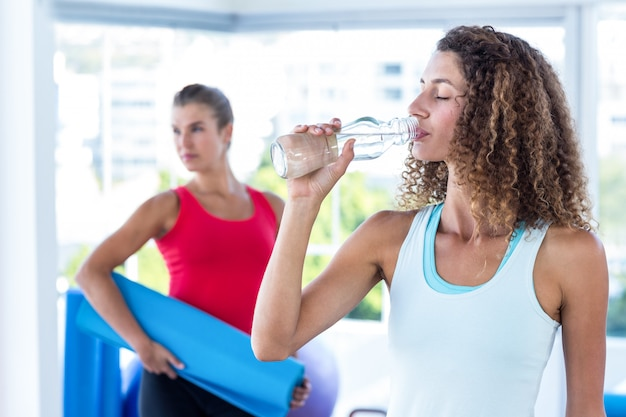 Mulher bebendo água no estúdio de fitness da garrafa