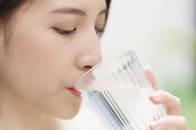 Mulher bebendo água, olho de foco