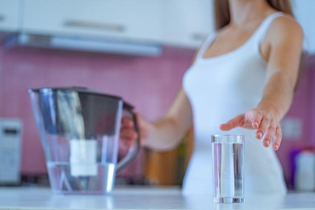 Mulher bebendo bebe água limpa e purificada de um filtro de água de manhã na cozinha em casa