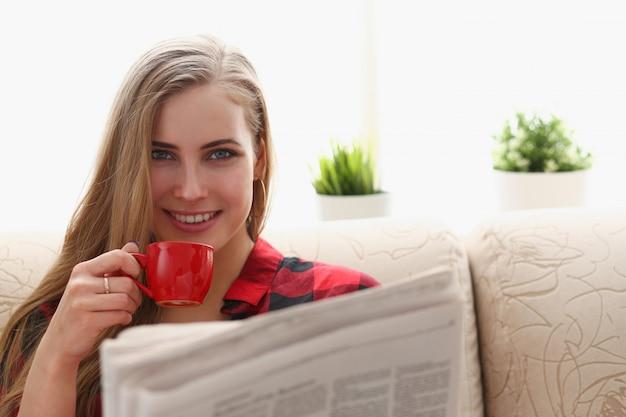 Mulher, bebendo café, e, leitura, sentar sofá