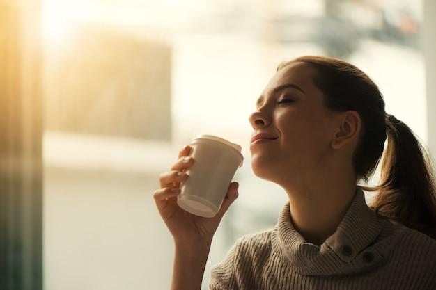 Mulher bebendo café em casa com o nascer do sol fluindo através da janela e criando flare nas lentes.