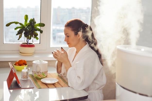 Mulher bebendo chá e lendo tablet perto do umidificador