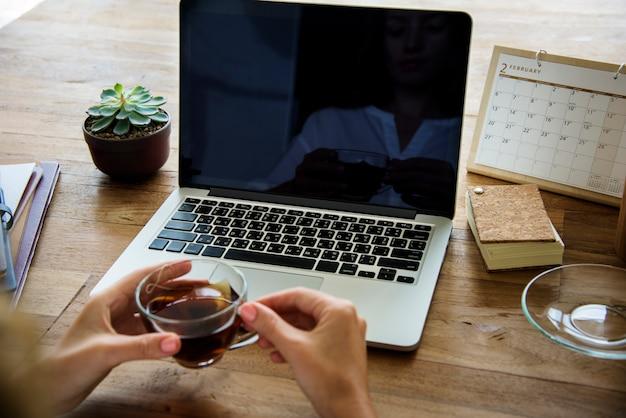 Mulher bebendo chá na mesa de madeira