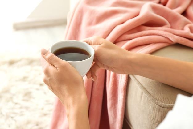 Mulher bebendo chá quente em casa, closeup
