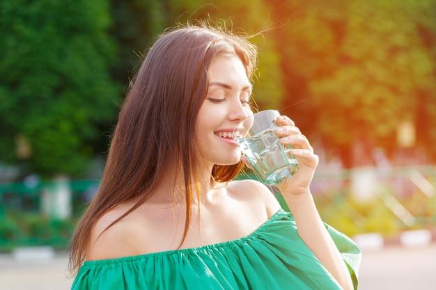 Mulher bebendo de um copo de água. foto do conceito de cuidados de saúde