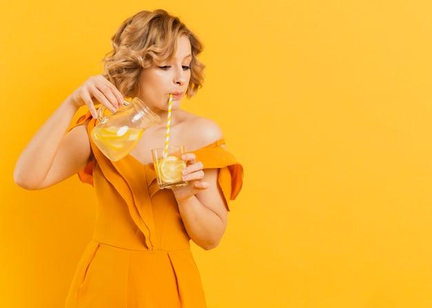 Mulher bebendo e derramando limonada