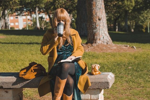 Mulher bebendo e lendo livro no parque