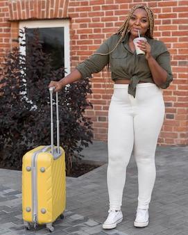 Mulher bebendo e parada ao lado de sua bagagem