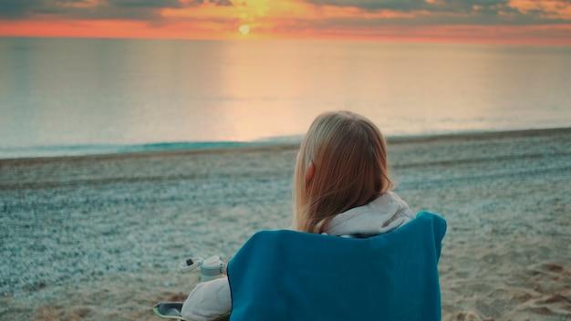 Mulher bebendo em uma caneca térmica e sentada na praia antes do nascer do sol