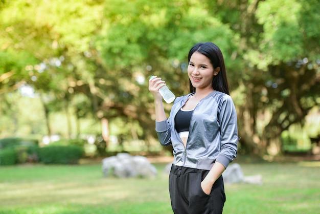 Mulher, bebendo, garrafa água, conceito saúde, miling, menina jovem, relaxe, exercício, e, segure garrafa água