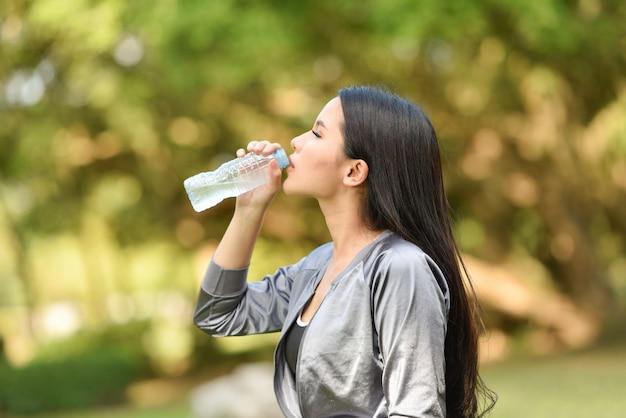 Mulher, bebendo, garrafa água, saúde, conceito, sorrindo, menina jovem, relaxe